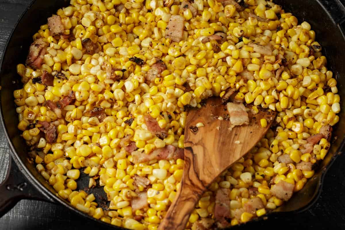 Corn and bacon cooking in a skillet.