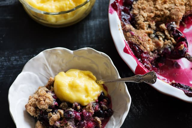 A spoonful of lemon curd on top of a berry crisp