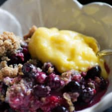 Bumbleberry Crisp in a bowl with a scoop of lemon curd
