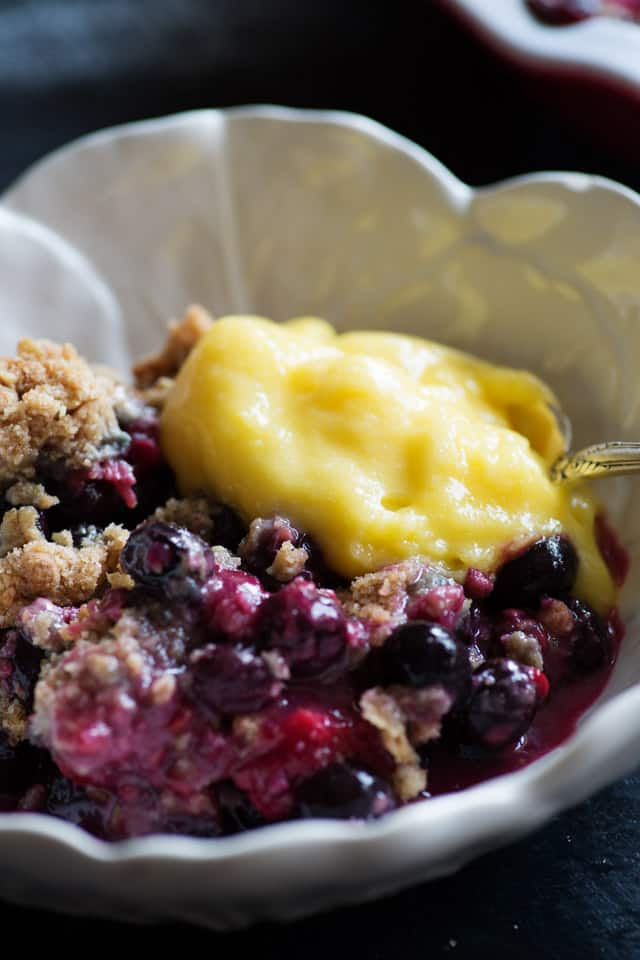 A white dish of bumbleberry crisp topped with lemon curd