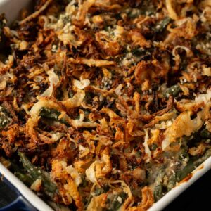 A casserole dish of green bean casserole topped with crispy onions.
