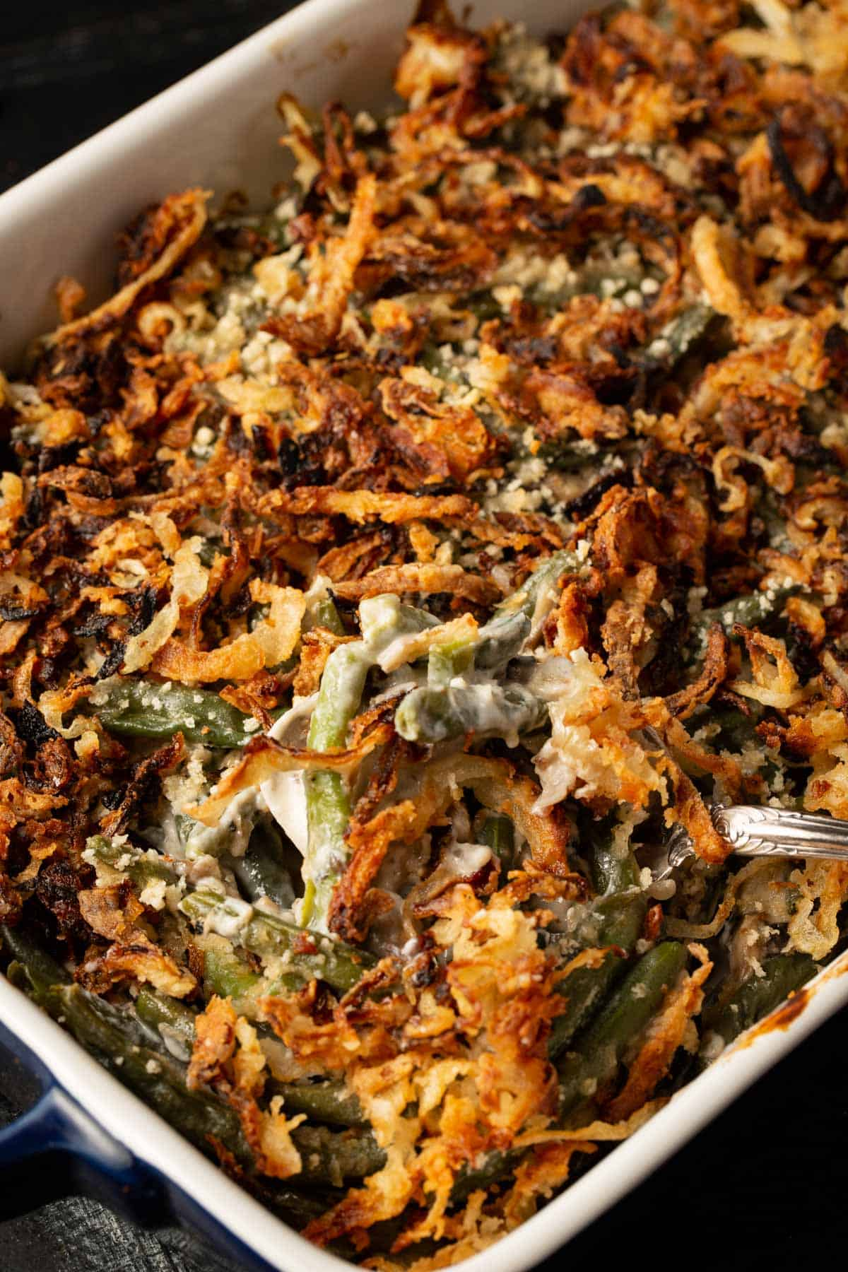 Green bean casserole made with fresh green beans with a serving spoon.