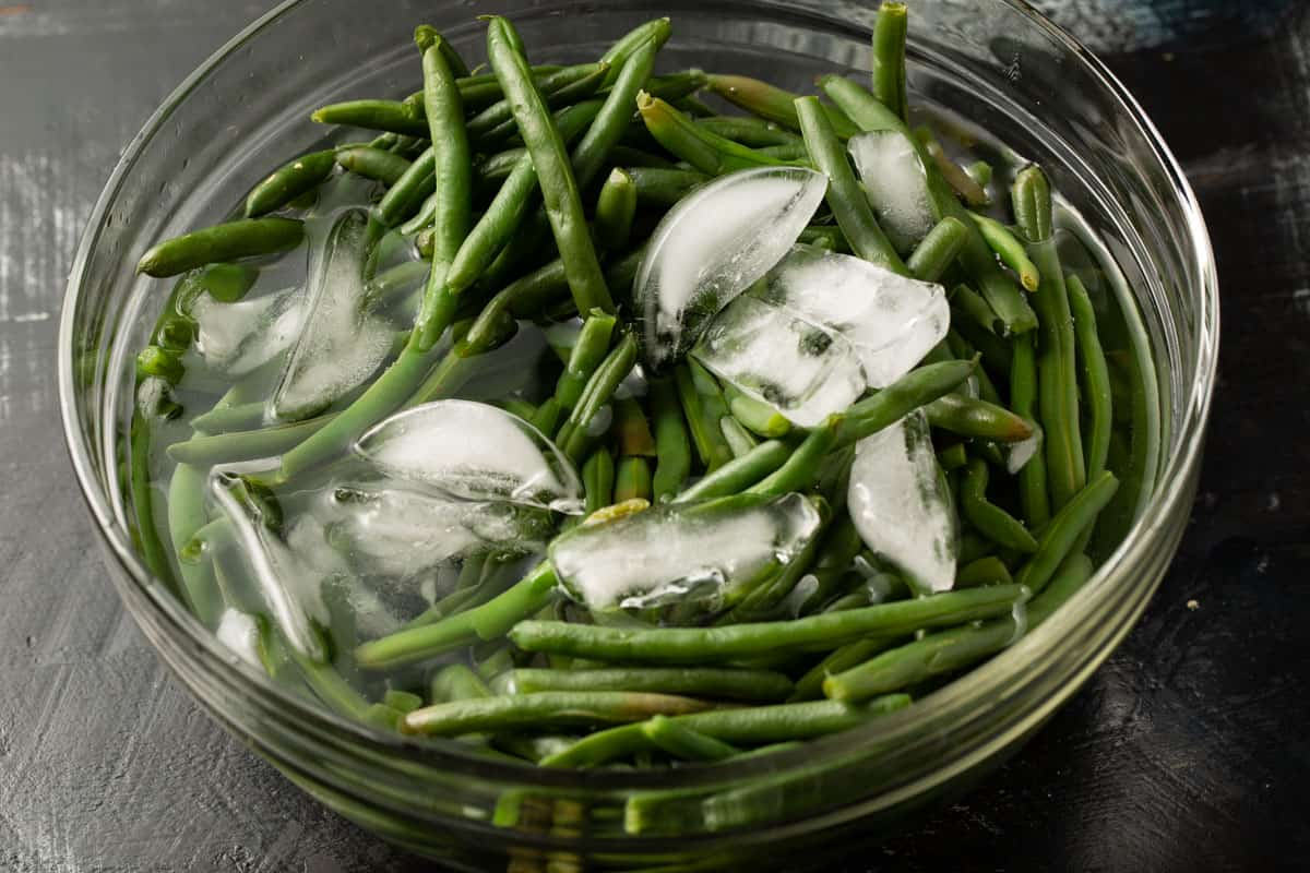 Green beans in a bowl of ice water.
