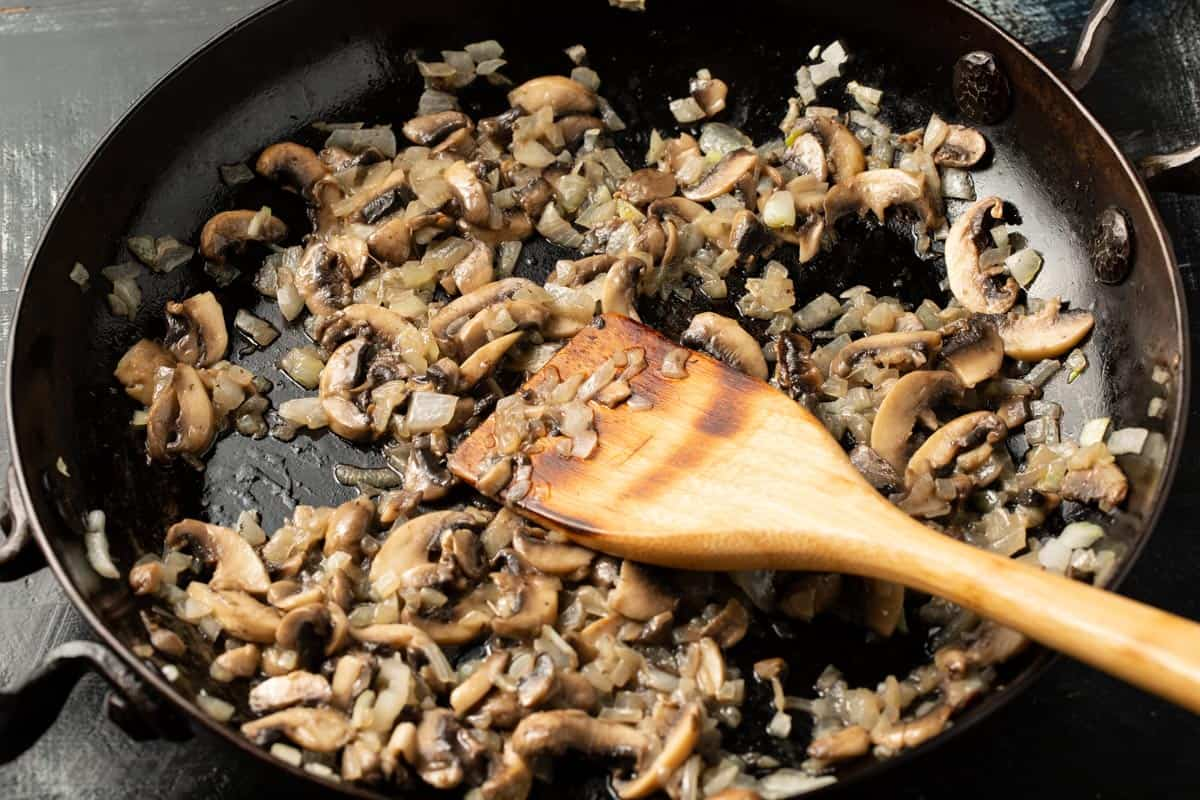 Mushrooms and onions cooking in a skillet.