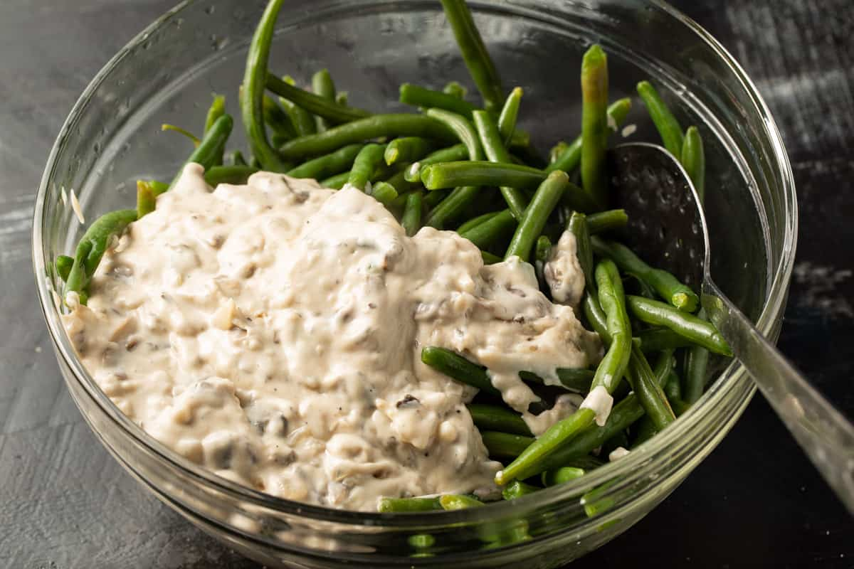 A bowl of cooked green beans with mushroom sauce.