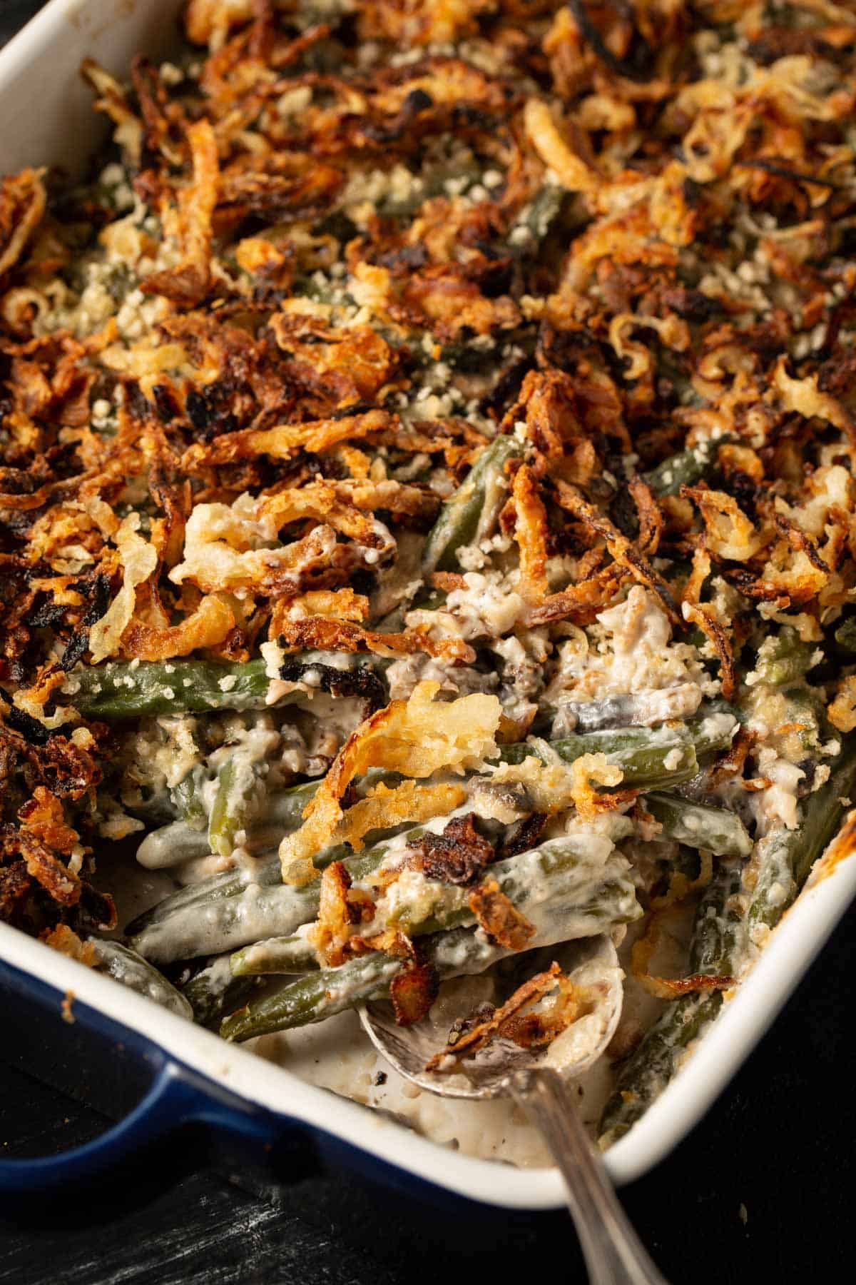 A serving spoon in a green bean casserole made from scratch,