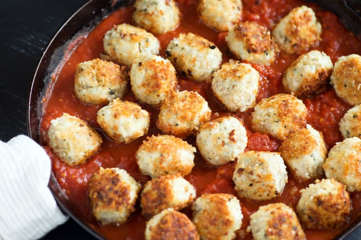 A skillet of chicken parmesan meatballs without cheese