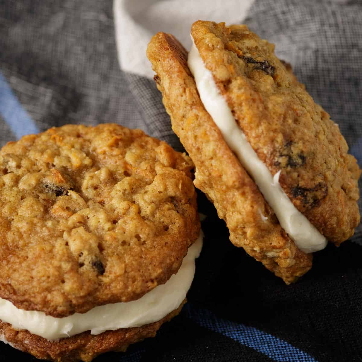 Two carrot cake sandwich cookies propped up and laying on a napkin