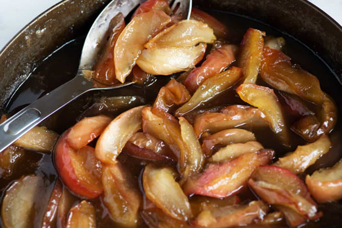 A spoon full of cooked apples in a skillet.