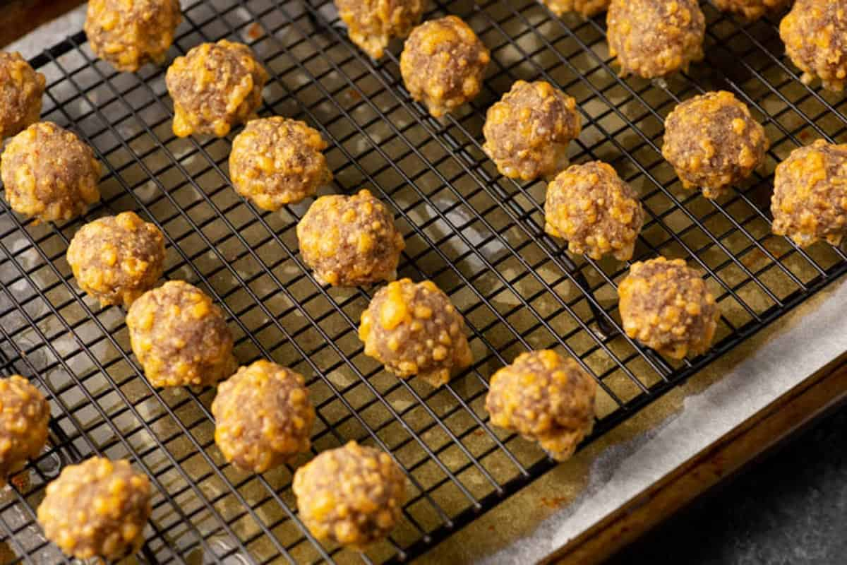 Baked sausage balls on a wire rack.