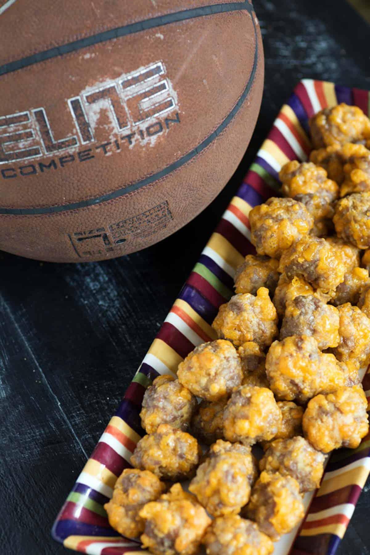 A platter of sausage balls next to a basketball.