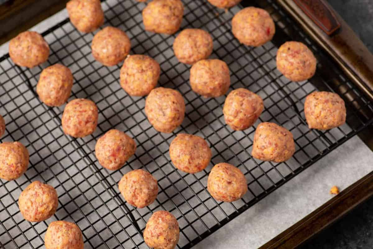 Sausage balls on a wire rack before they have been baked.