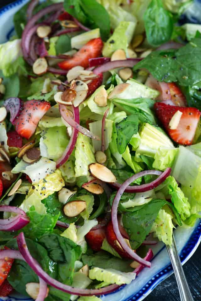 Strawberry spinach salad with toasted almonds on a platter