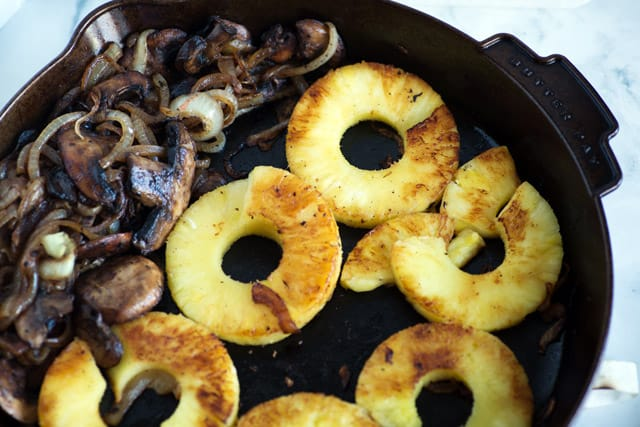 A skillet with mushrooms, onions and pineapple for Pineapple Burgers