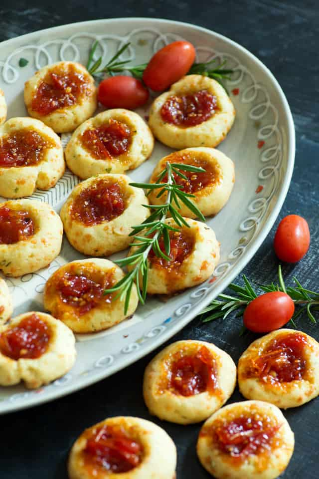 Savory Thumbprint Cookies on platter with tomatoes and rosemary
