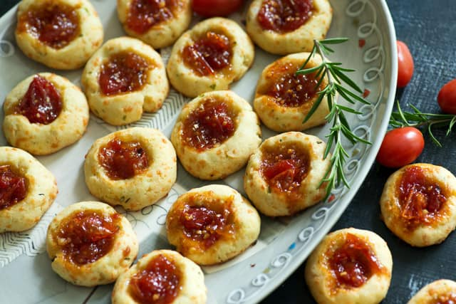 Savory Thumbprint Cookies with Bourbon Tomato Jam - the perfect appetizer for any event, great at room temperature and sure to surprise when they bite into a savory cookie filled with a spicy bourbon flavored tomato jam | butterandbaggage.com