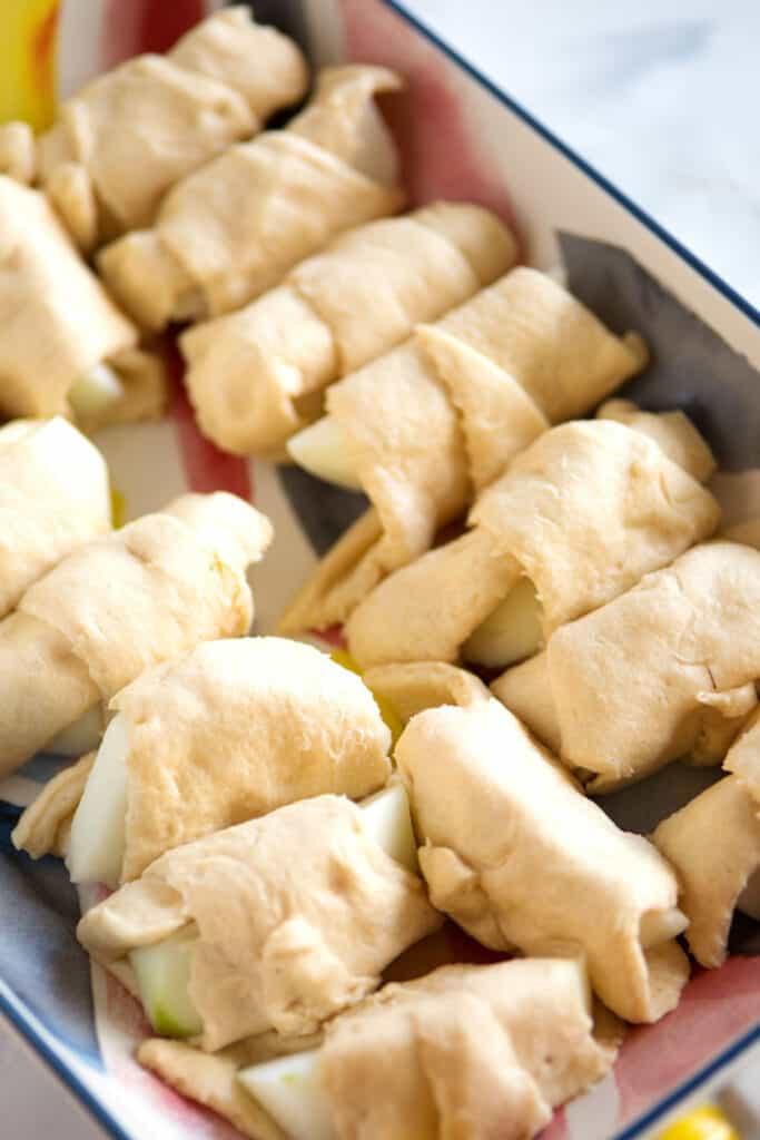 A baking dish with raw apple dumplings.