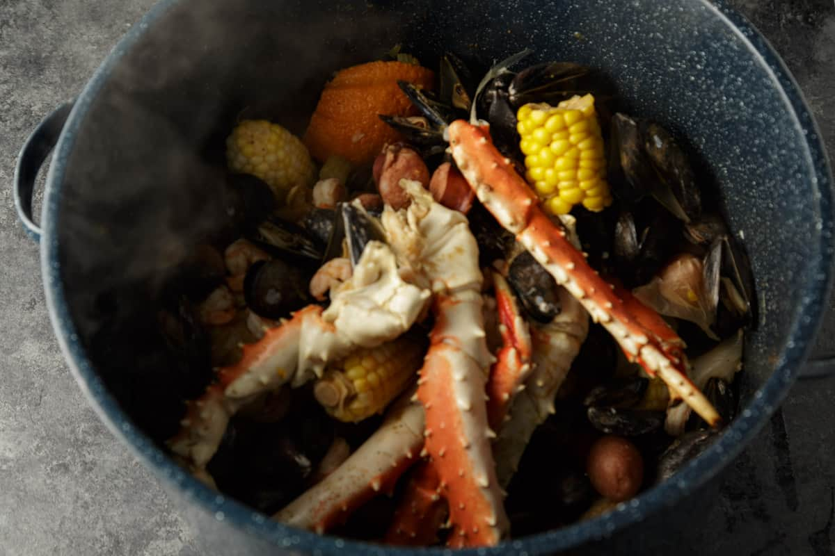 A pot full of all the ingredients for a seafood boil