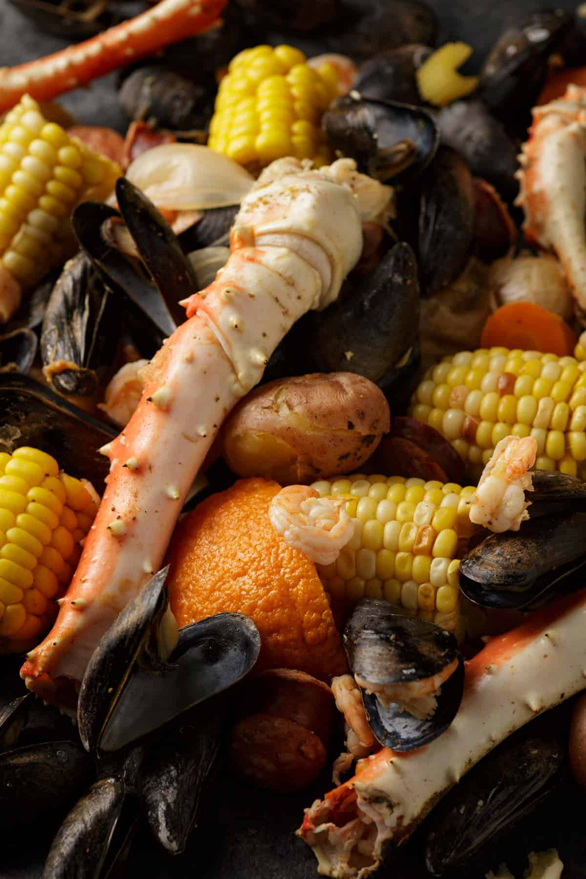 Crab legs and corn with mussels and shrimp on a platter