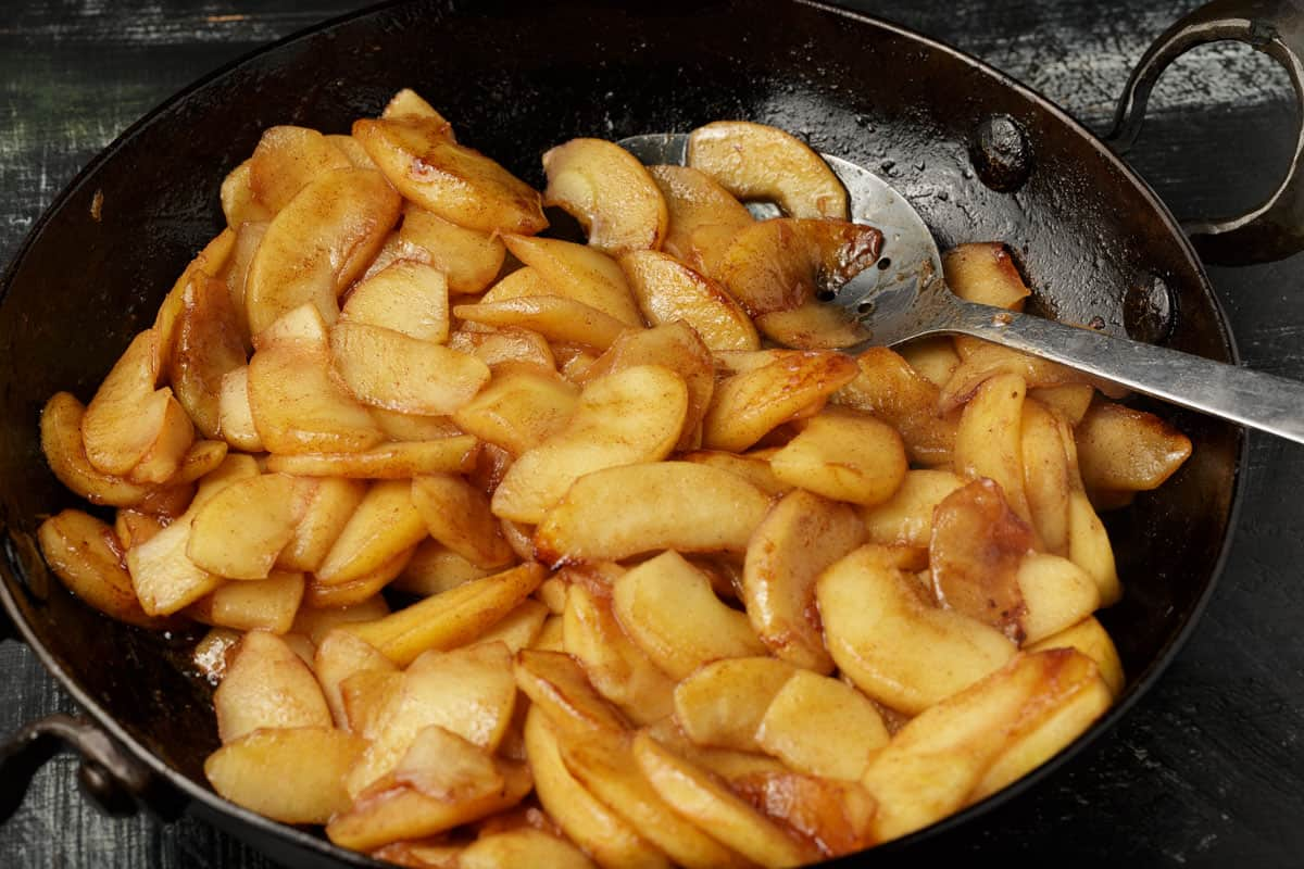 Sliced apples cooked in a skillet.