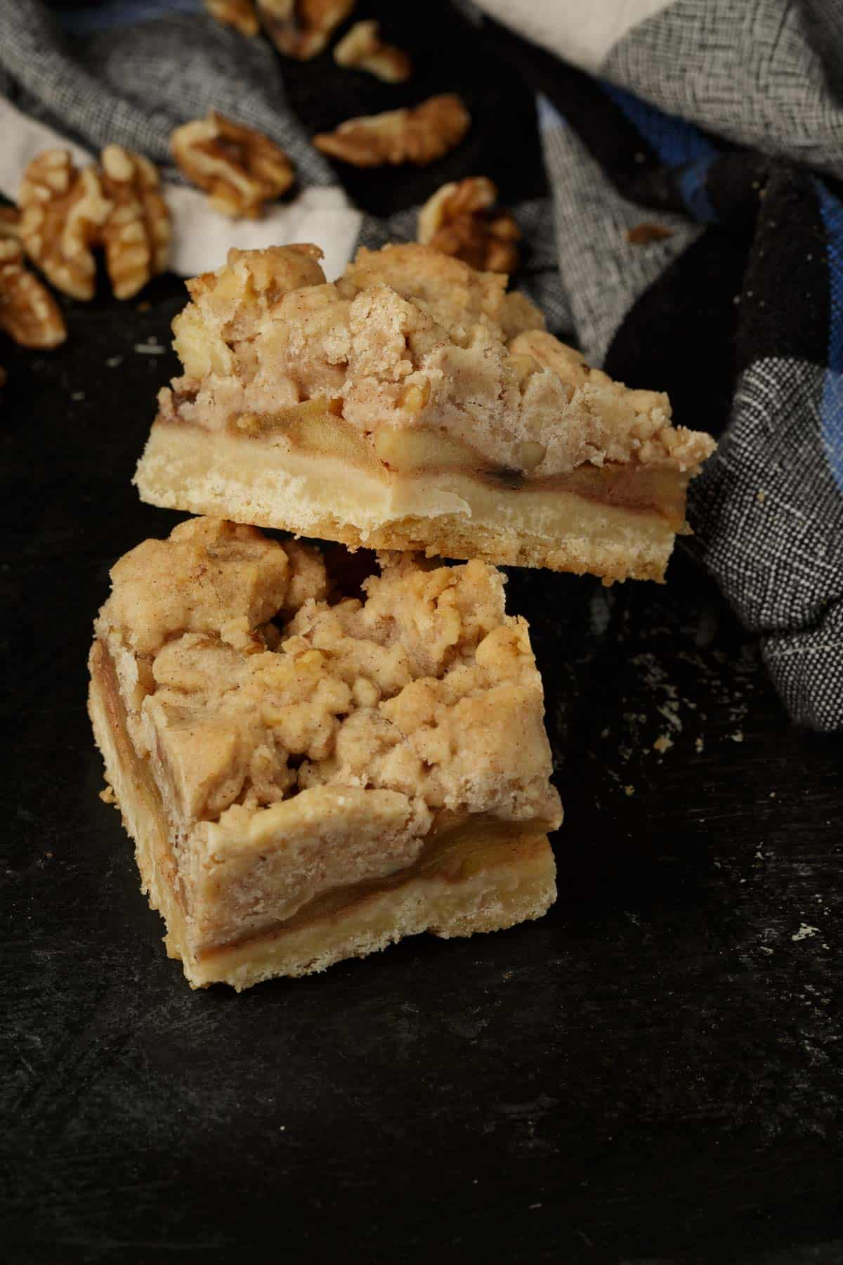 Two apple bars stacked with walnuts in the background.