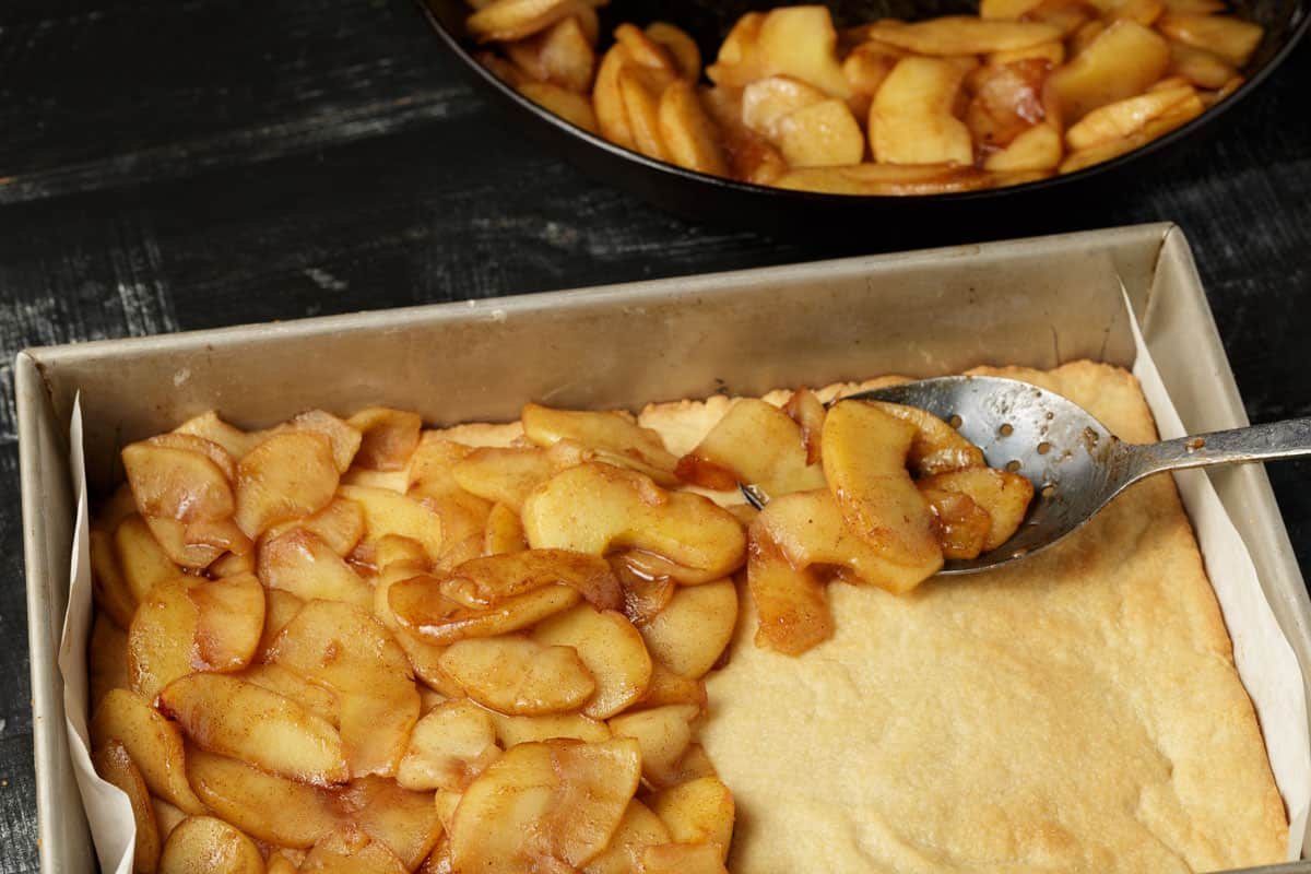 Apples being spooned onto a baked crust.