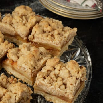 A clear glass platter filled with apple bars.