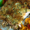 Baked salmon with herbed butter on parchment paper