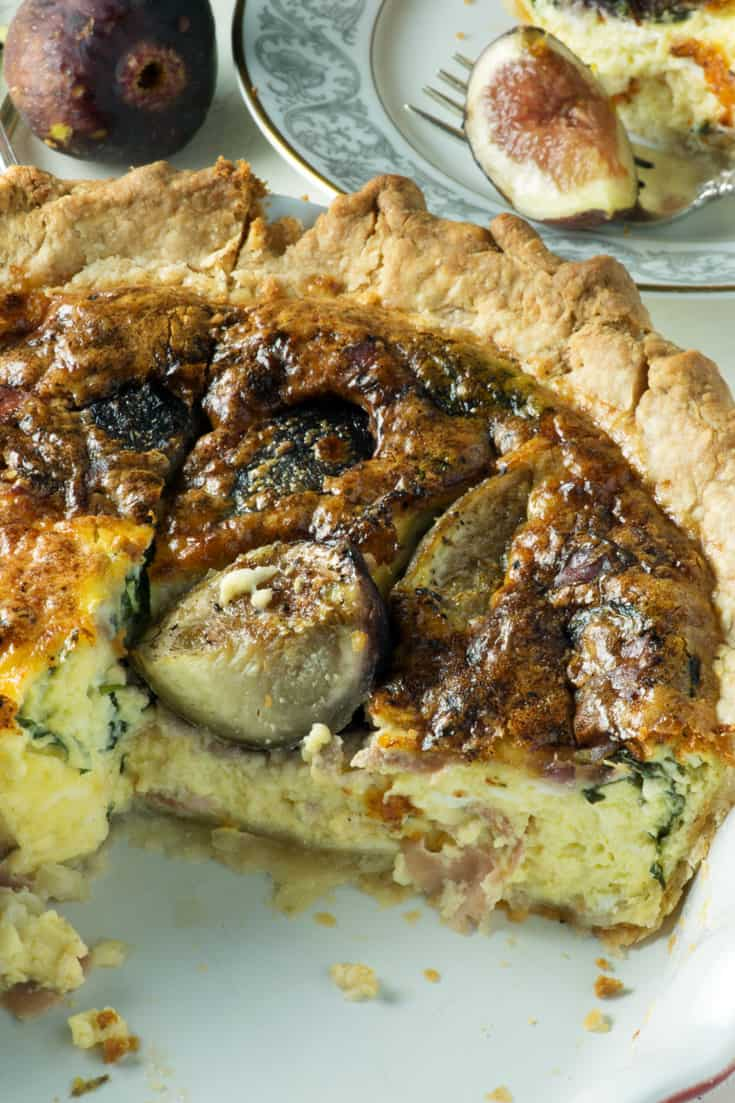 Slice of Quiche with figs and prosciutto on plate with fork and figs