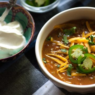 A bowl of Instant Pot chili with sour cream and cheese