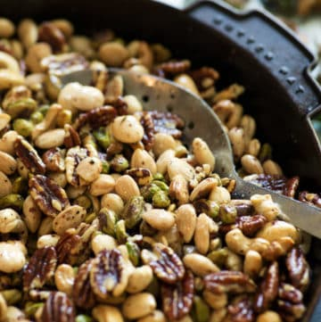 Roasted nuts with sage and rosemary in a skillet