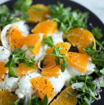 A plate of burrata and orange slices