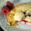 A raspberry hand pie on a plate with a fork