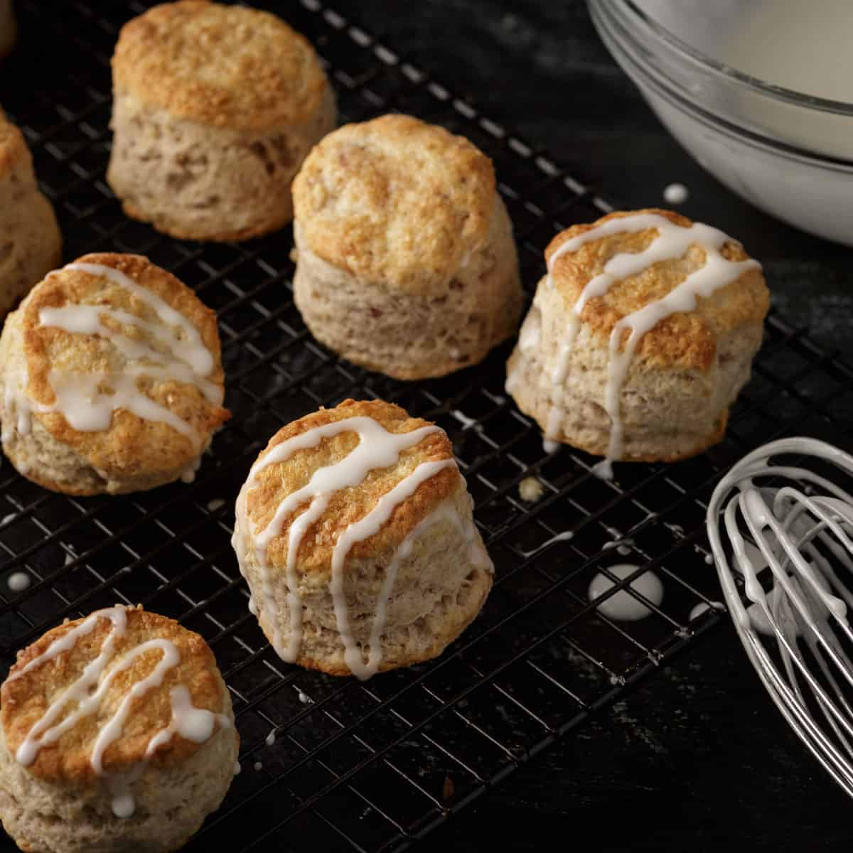 Strawberry biscuits on a rack with a glaze drizzled across the top