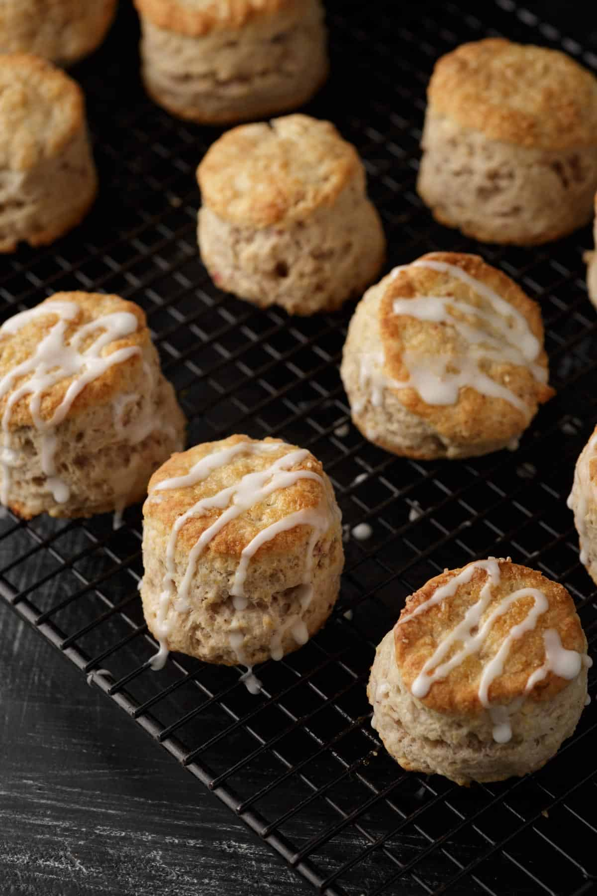 A cooling rack of mini biscuits with a glaze drizzled on top