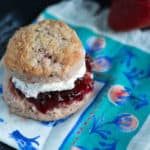 strawberry biscuit with jam and cream on a napkin