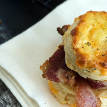 A biscuit with bacon on a napkin