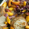 A sheet pan of pork chops and peaches