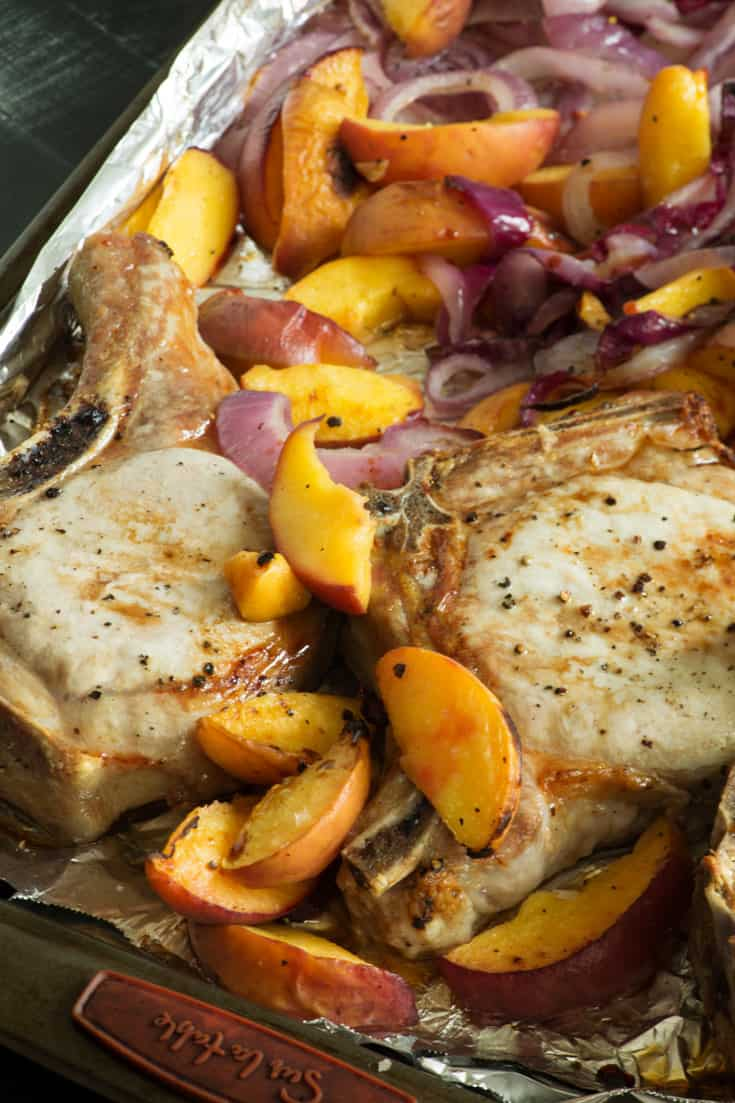 A sheet pan with pork chops and peaches