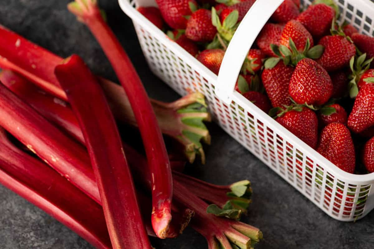 A basket of strawberries and stalks of rhubarb