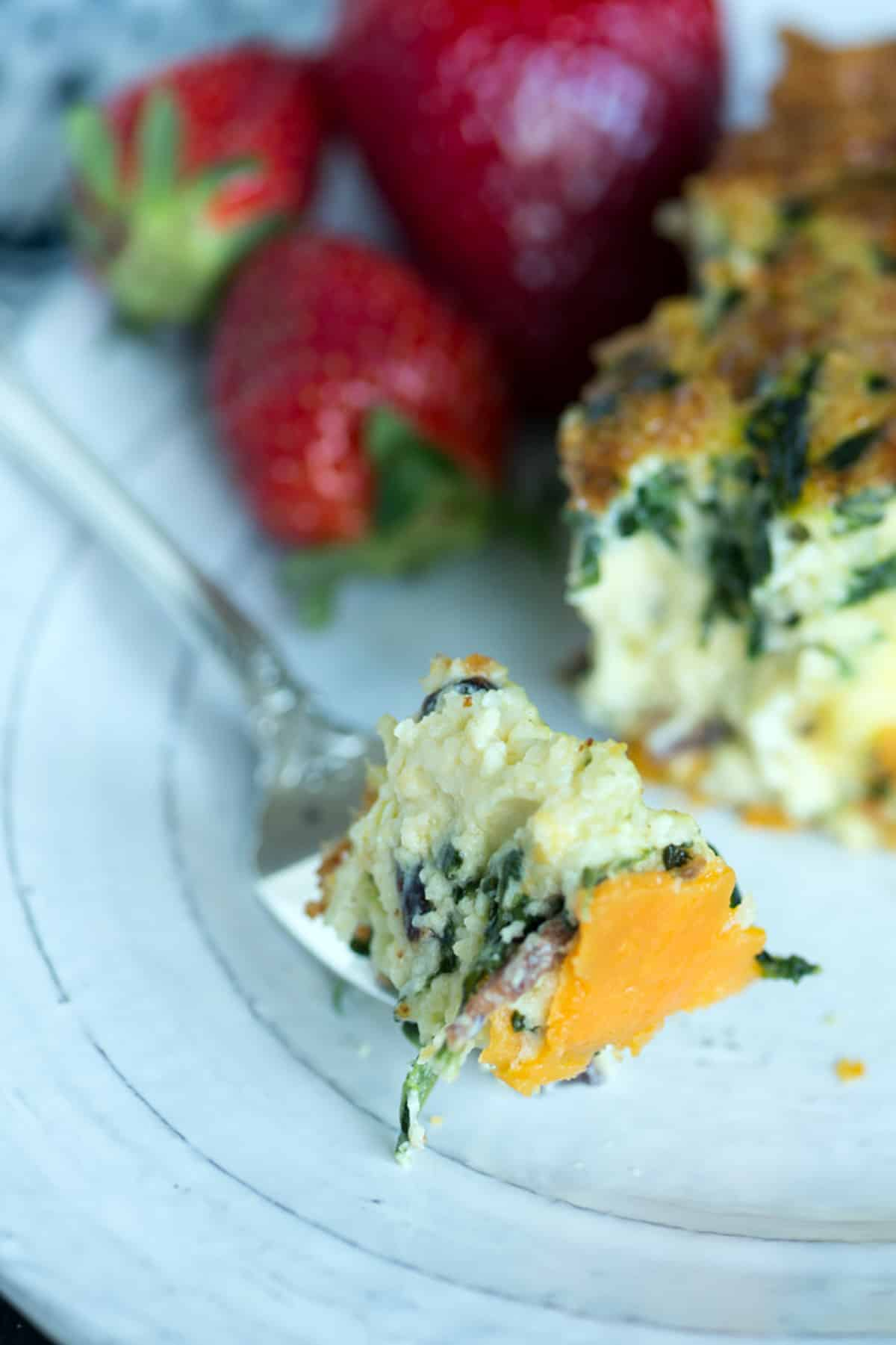 A bite of quiche with a sweet potato crust