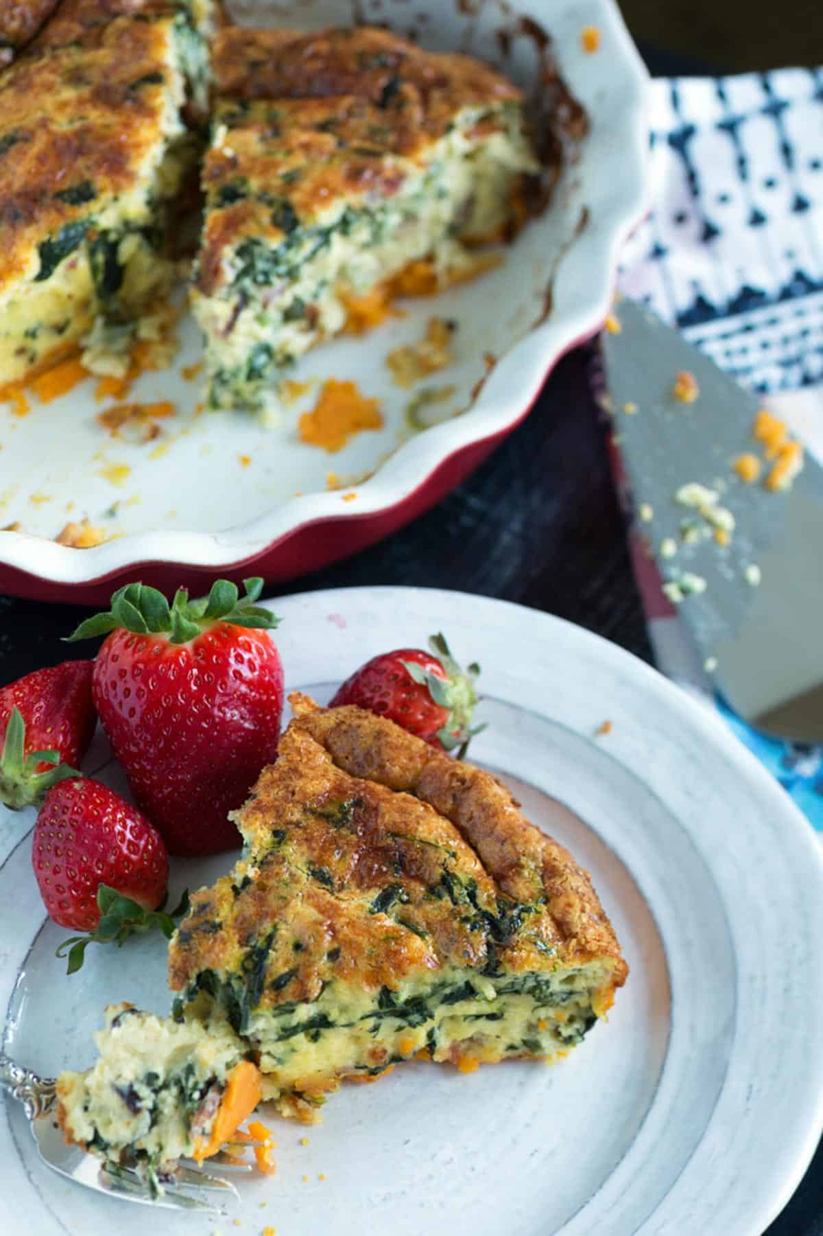 A slice of sweet potato crust quiche with a strawberry