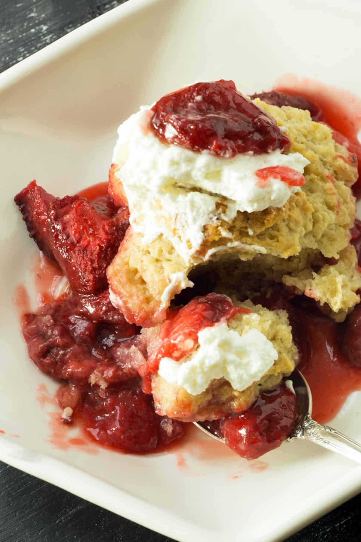 A serving of strawberry cobbler with whipped cream