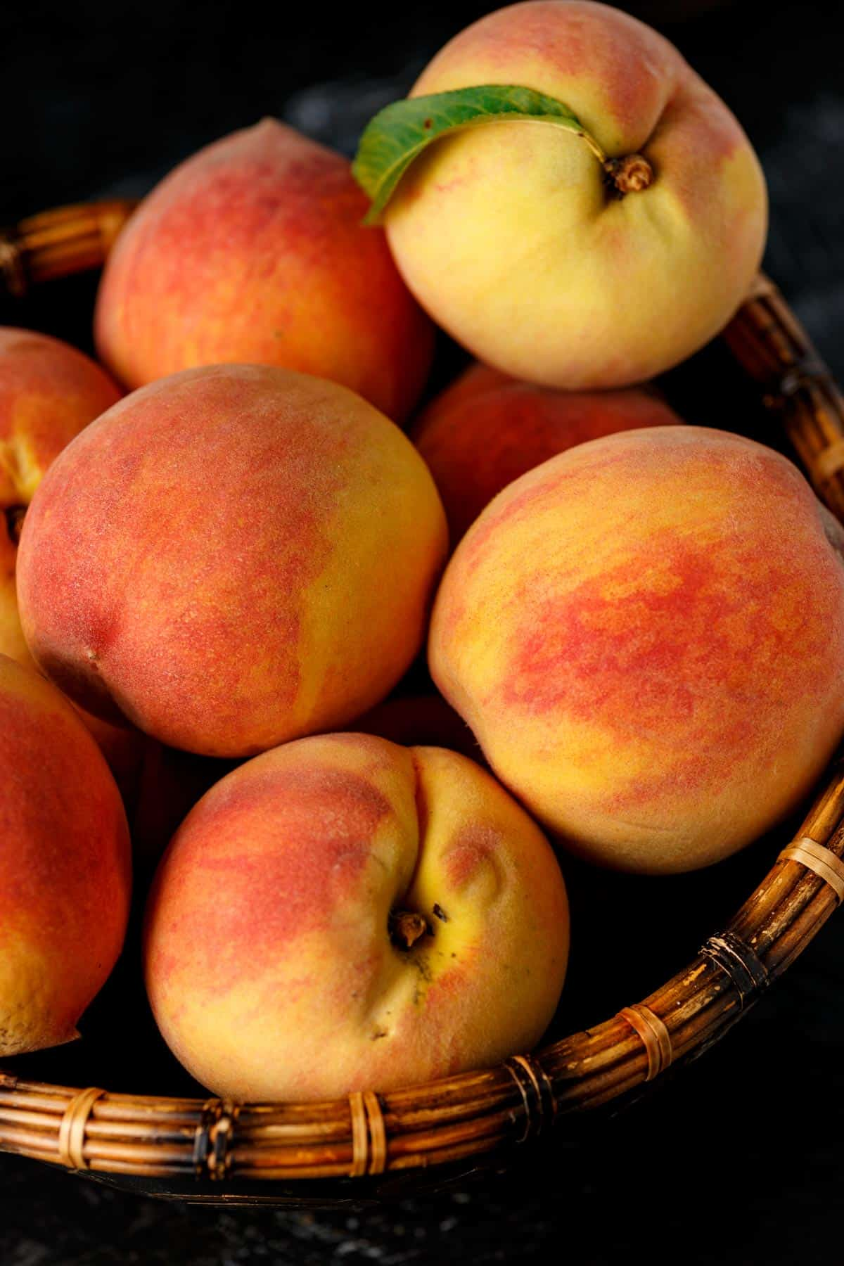 A wooden basket full of peaches