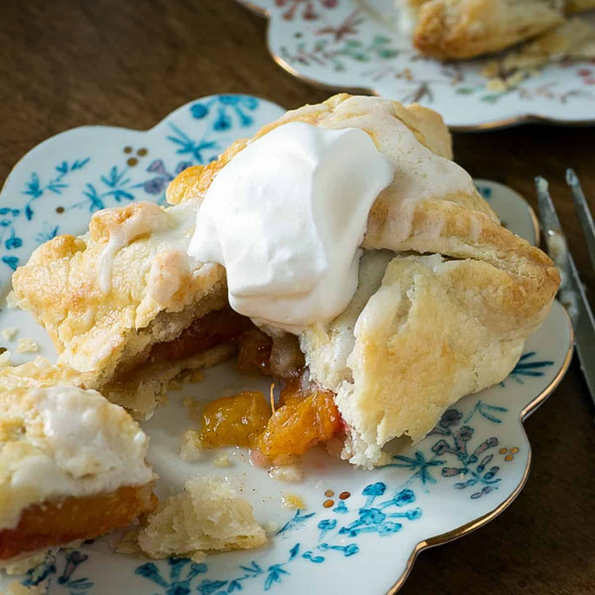 A peach dumpling topped with whipped cream with a bite taken out