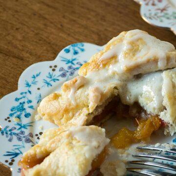 A dessert plate with a peach dumpling on top