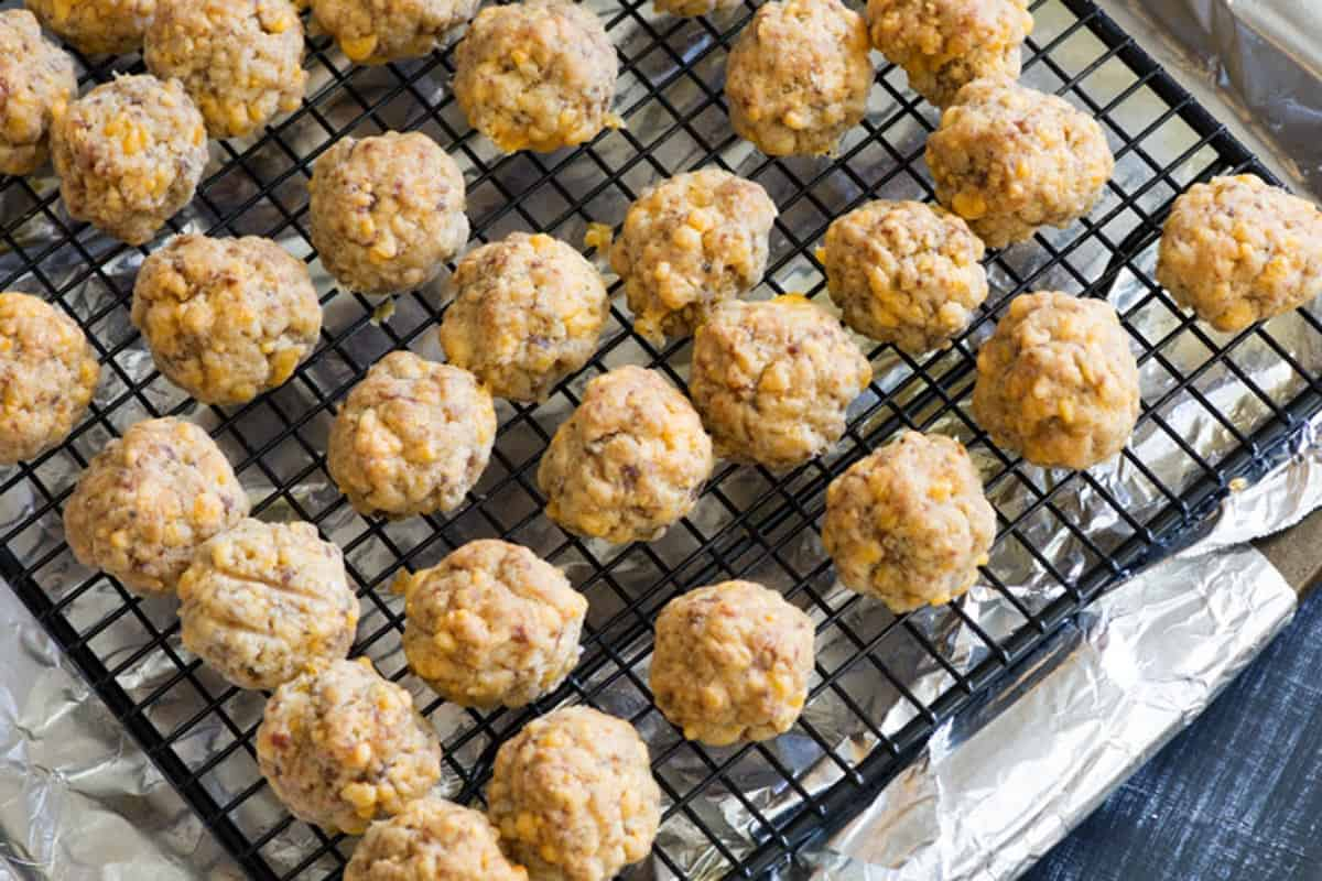 A baking sheet with a rack on it with sausage balls.