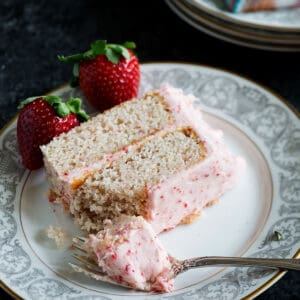 A bite out of a slice of strawberry cake