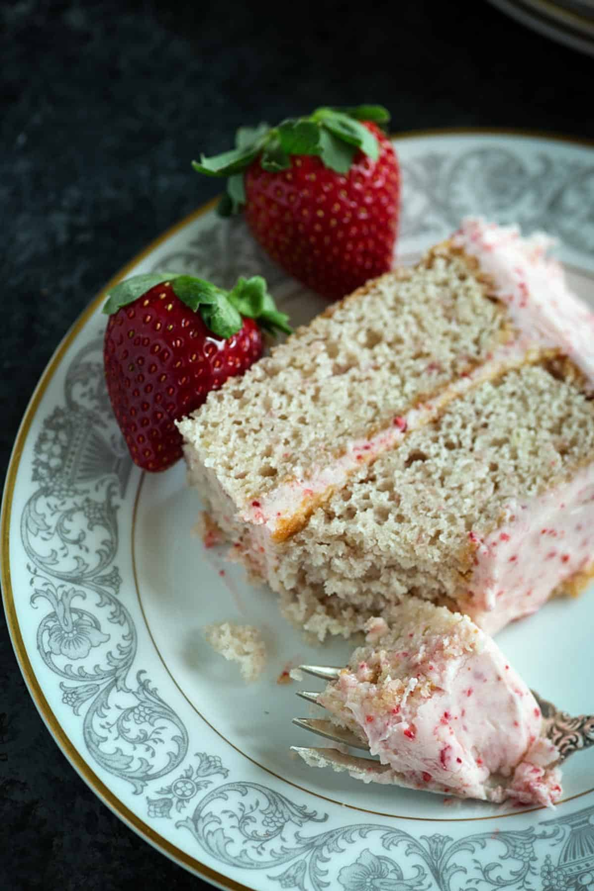 A bite of strawberry cake on a plate