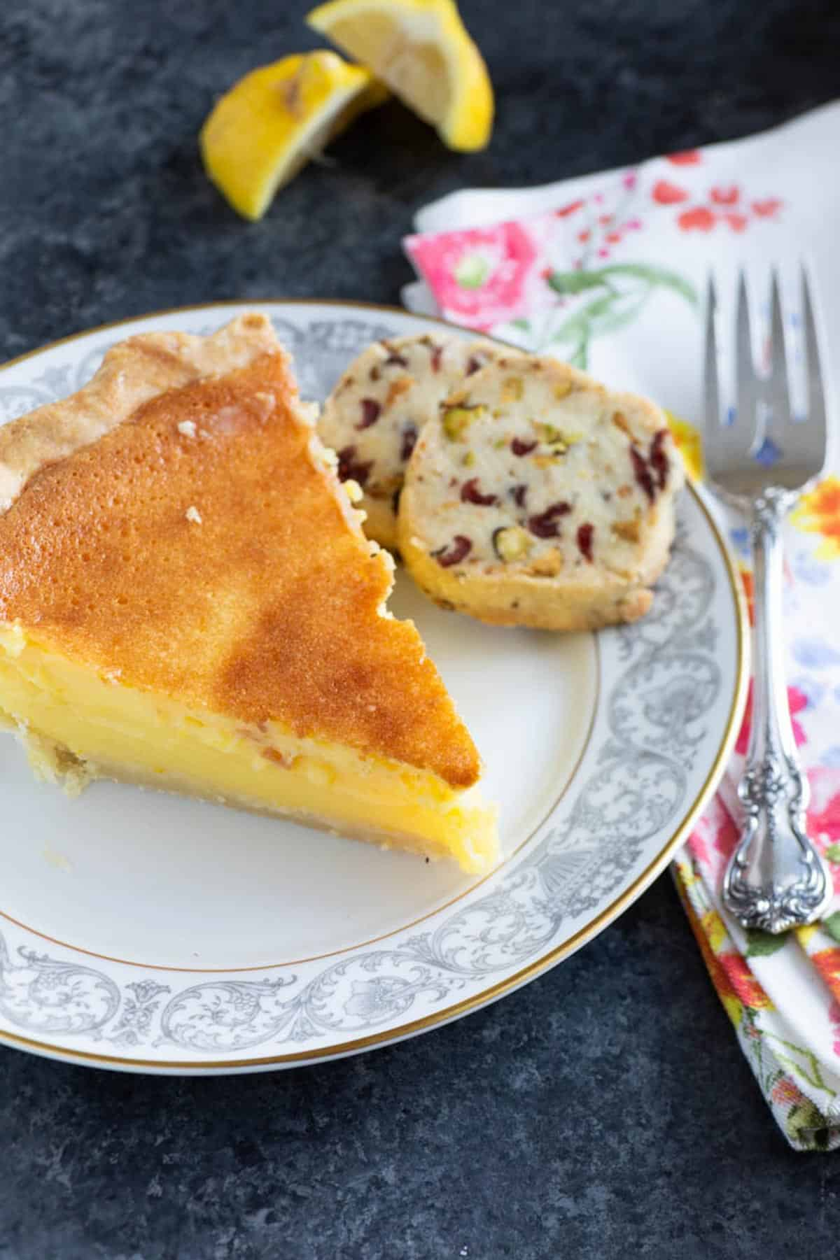 A slice of lemon chess pie with a shortbread cookie on a plate.